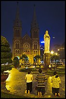Family in prayer outside Notre-Dame Basilica at night. Ho Chi Minh City, Vietnam ( color)