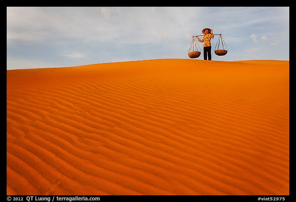 Woman on top of red sand dunes. Mui Ne, Vietnam (color)