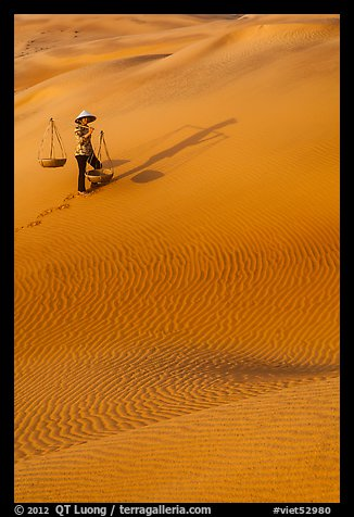 Woman with yoke baskets on sands. Mui Ne, Vietnam (color)