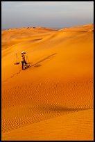Rippled red sand dunes and woman with baskets. Mui Ne, Vietnam (color)