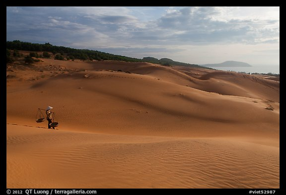 Coastal sand dunes with sea in distance and local woman. Mui Ne, Vietnam (color)