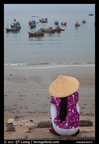 Woman with conical hat sitting above fishing fleet. Mui Ne, Vietnam (color)
