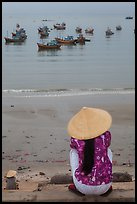 Woman with conical hat sitting above fishing fleet. Mui Ne, Vietnam ( color)