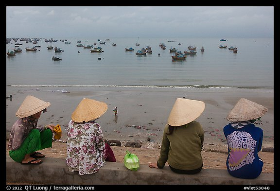 Four women in conical hats watch fishing activity from high above fishing village. Mui Ne, Vietnam (color)