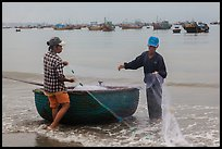 Man and woman gathering fishing net onto roundboat. Mui Ne, Vietnam (color)