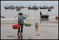 Woman with yoke baskets on beach. Mui Ne, Vietnam (color)