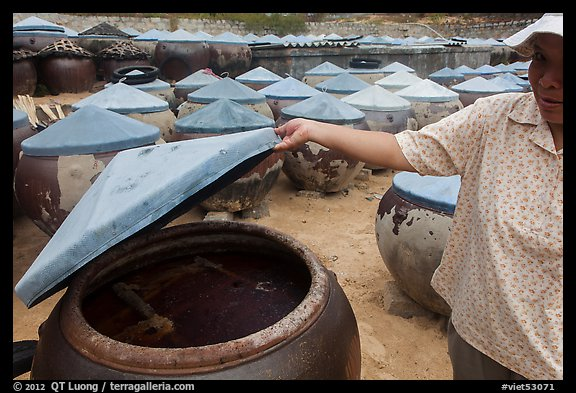 Woman examining vat of fish sauch. Mui Ne, Vietnam (color)