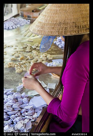 Woman wearing conical hat wrapping coconut candy, Phoenix Island. My Tho, Vietnam (color)