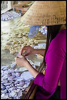 Woman wearing conical hat wrapping coconut candy, Phoenix Island. My Tho, Vietnam ( color)