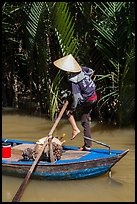 Woman standing in canoe on jungle canal, Phoenix Island. Mekong Delta, Vietnam (color)