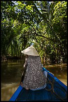 Woman rowing boat under jungle canopy, Phoenix Island. Mekong Delta, Vietnam (color)