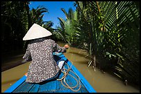 Woman rowing boat in canal lined up with vegetation, Phoenix Island. Mekong Delta, Vietnam (color)