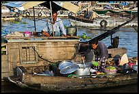 Woman serving food across boats, Cai Rang floating market. Can Tho, Vietnam (color)
