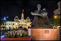 Ho Chi Minh as teacher bronze by Diep Minh Chau and City Hall by night. Ho Chi Minh City, Vietnam (color)