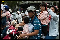 Family on motorbike watching musical performance. Ho Chi Minh City, Vietnam (color)
