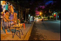 Woman tends to altar on street at dusk. Hoi An, Vietnam (color)