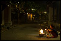 Woman burning paper on street at night. Hoi An, Vietnam ( color)