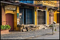 Woman carrying fruit in front of old storefronts. Hoi An, Vietnam (color)