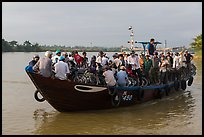 People crossing river on small ferry. Hoi An, Vietnam (color)