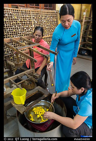Workers demonstrate silkworm processing. Hoi An, Vietnam (color)