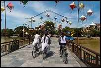 Girls on bicycle cross bridge festoned with lanterns. Hoi An, Vietnam ( color)