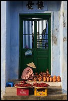 Ceramics vendor, blue temple door. Hoi An, Vietnam (color)