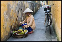 Fruit vendor in narrow alley. Hoi An, Vietnam (color)