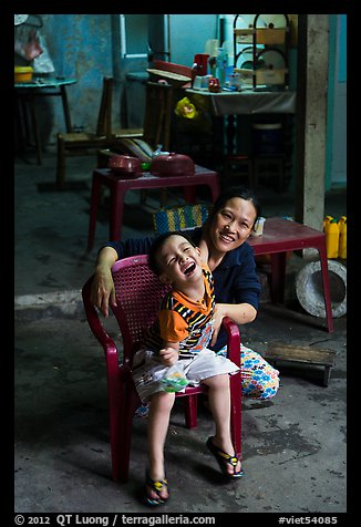 Boy and woman in kitchen. Hoi An, Vietnam (color)