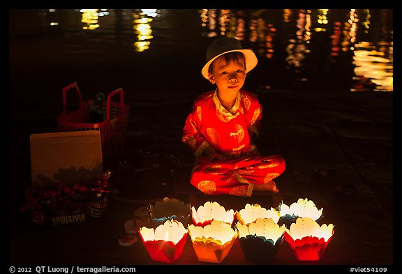 Boy selling candle lanterns at night. Hoi An, Vietnam (color)