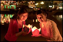 Two women lighted by candle box at night. Hoi An, Vietnam (color)