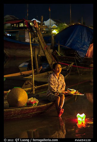 Woman sitting in boat with floating candles by night. Hoi An, Vietnam (color)