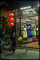 Women with bicycles in front of taylor shop. Hoi An, Vietnam ( color)