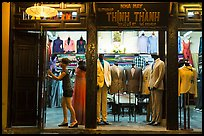 Woman closing doors of taylor shop. Hoi An, Vietnam (color)