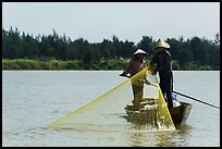 Fishermen standing in boat retrieving net, Thu Bon River. Hoi An, Vietnam ( color)