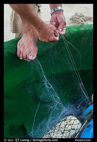 Close-up of hands and feet of man mending net. Da Nang, Vietnam (color)