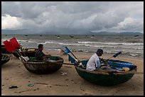 Fishermen mending nets in coracle boats. Da Nang, Vietnam ( color)