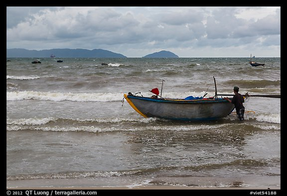Man entering ocean with boat in stormy weather. Da Nang, Vietnam (color)