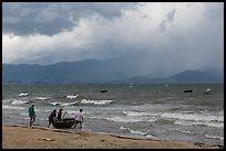 Men pushing coracle boat into stormy ocean. Da Nang, Vietnam (color)