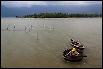 Man rowing coracle boat in lagoon. Vietnam ( color)