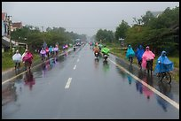 Riders wearing colorful ponchos on wet road on Hwy 1 south of Hue. Vietnam (color)