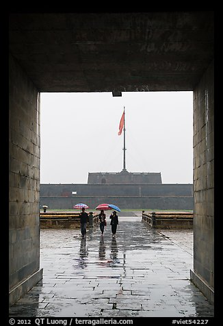 Tourists with unbrellas and flag monument, citadel. Hue, Vietnam (color)