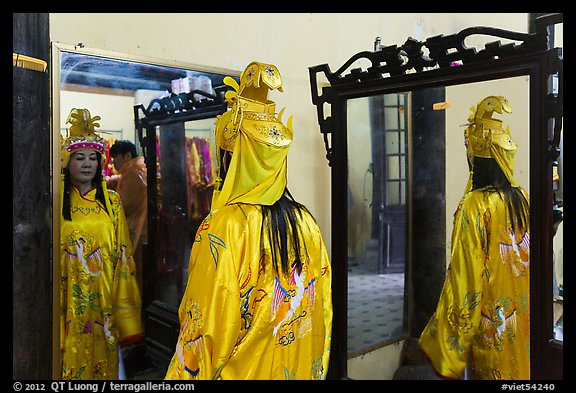 Woman in imperial dress checking herself in mirror, citadel. Hue, Vietnam (color)