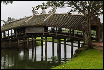 Friends sitting inside covered bridge, Thanh Toan. Hue, Vietnam ( color)