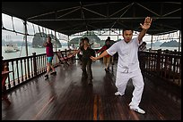 Morning Tai Chi session on tour boat deck. Halong Bay, Vietnam (color)