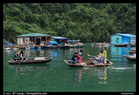 Villagers move between floating houses by rowboat. Halong Bay, Vietnam (color)