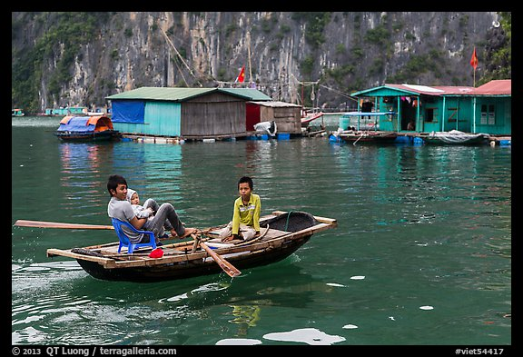 Man holding infant while rowing with feet, Vung Vieng village. Halong Bay, Vietnam (color)