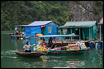 Woman buying produce from grocery boat, Vung Vieng village. Halong Bay, Vietnam (color)