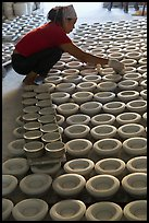 Woman laying ceramic bowls to dry in workshop. Bat Trang, Vietnam (color)