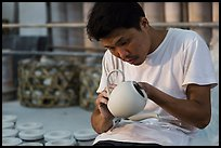 Man assembling ceramic tea pot in workshop. Bat Trang, Vietnam (color)