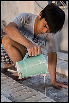 Man pouring clay into molds in ceramic workshop. Bat Trang, Vietnam (color)